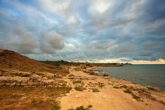 Cloudy sunset at the coast. Sunset over a rocky coast with the cloudy sky stock images