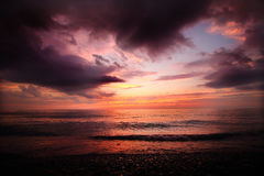 Cloudy Sunset on a Lake Erie Beach. Purple-ish, Orange-ish sunset on a rocky Lake Erie beach. Calm waves, dark ominous clouds royalty free stock photo