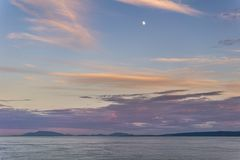 Cloudy sunset and moon in strait of Georgia between Vancouver and Victoria. Cloudy sunset and moon in strait of Georgia between Vancouver and Victoria stock photos