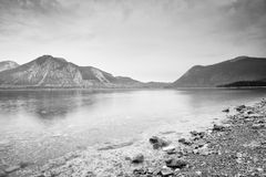 Cloudy sunset at mountain lake. Stony beach and dark mountains Stock Images