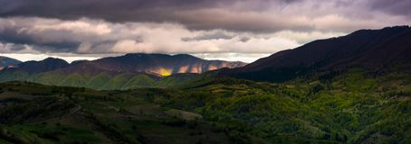 Cloudy sunset in mountainous countryside. Panorama of cloudy sunset in mountainous countryside. beautiful springtime landscape with ridge in the distance. rural Stock Image