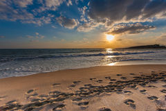 Cloudy sunset over a deserted beach. Beautiful tranquil cloudy sunset over a deserted beach with the fiery orange orb of the sun low in the sky casting a path stock photos