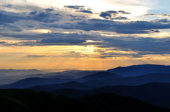 Cloudy sunset over emerald mountain ridges Royalty Free Stock Images
