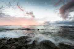 Cloudy Sunset Over Horizon, Waves Crashing Over Rocks Stock Image