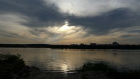 Cloudy sunset over a lake with a sunny path on it in summer. A gorgeous view of a beautiful lake with a romantic sun path on a wild lake in Ukraine in summer stock video
