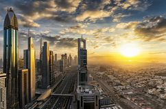Cloudy sunset over the modern skyline of Dubai, UAE. With reflections in the diverse skyscrapers and buildings royalty free stock images