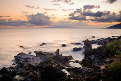 Cloudy Sunset over Ocean and Rocky Shore Time Lapse Photo Royalty Free Stock Images