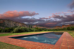 Cloudy sunset with red rock hills reflect in rectangular pool Stock Image