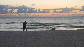 Cloudy sunset in the sea. Sunset with walking couple royalty free stock images