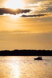 Cloudy sunset with silhouette of lonely boat Royalty Free Stock Photo