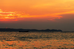 Cloudy sunset with silhouette of lonely boat Stock Images