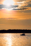 Cloudy sunset with silhouette of lonely boat Royalty Free Stock Photos