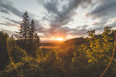 Cloudy sunset view over forest and lush valley with lens flare. The sun goes down in a lush, forested area Stock Photo