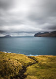 Cloudy And Windy Evening View of Road, Ocean and island in The Horizon. Faroe islands, Denmark,Europe Royalty Free Stock Image