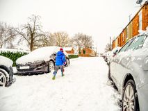Cloudy winter day view of young boy running on typical snowy british road between parked cars in blue jacket and festive. Hat Royalty Free Stock Photo