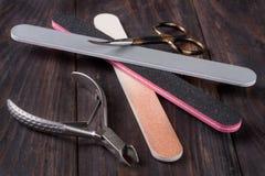 Clouez les ciseaux classent et des tondeuses pour enlever les produits de soin de cuticle sur un fond en bois foncé Photos libres de droits