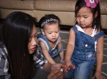Clous asiatiques de filles de peinture de mère Photographie stock libre de droits