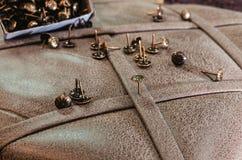 Clous décoratifs de meubles sur le fond de la tapisserie d'ameublement de tissu photo stock