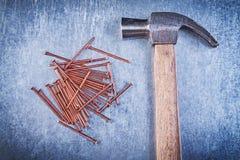 Clous de construction d'en cuivre de marteau de griffe de vintage sur le backgr métallique Photographie stock libre de droits