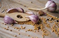 Clous de girofle d'ail, de graines de moutarde et de cuillère sur le conseil en bois Ail rustique de style sur le fond en bois de Photo libre de droits