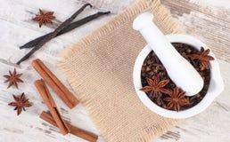Clous de girofle et anis parfumés en mortier et épices sur le conseil rustique Photos libres de droits