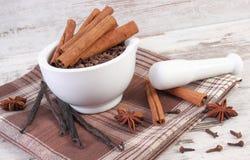 Clous de girofle et cannelle parfumés en mortier et épices sur le conseil rustique Photos stock