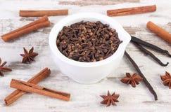 Clous de girofle parfumés en mortier et épices blancs sur le vieux conseil rustique Images stock