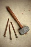 Clous et marteau avec des gouttelettes de sang Image stock