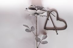 Clous faits main forgés en métal de coeur sur un fond blanc Rose et coeur forgés Configuration plate, concept minimal de vue supé illustration stock