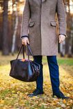 Clous up of the man in a coat and a leather bag in the beautiful autumn wood Royalty Free Stock Photos