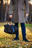 Clous up of the man in a coat and a leather bag in the beautiful autumn wood Royalty Free Stock Photography