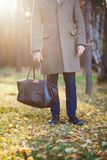 Clous up of the man in a coat and a leather bag in the beautiful autumn wood Royalty Free Stock Image