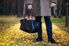 Clous up of the man in a coat and a leather bag in the beautiful autumn wood Royalty Free Stock Photo