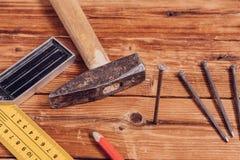 Clous, vieux marteau, crayon et angle de mesure sur le fond en bois photographie stock