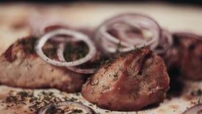 Clouse encima de la comida Kebab de la carne de cerdo con la cebolla y las hierbas, servidas en una hoja del pan Pita El cocinero almacen de video