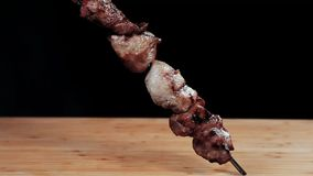 Clouse encima de la comida Kebab listo en el pincho Una mano da vuelta a un kebab en un pincho en una tabla de madera negro almacen de metraje de vídeo