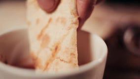 Clouse encima de la comida Pan Pita de las clavadas de la mano en una salsa roja metrajes