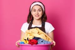 Clouse oben der schönen Hausfrau, arbeitend über Haus, hält enormes rosa Becken voll des schmutzigen Leinens, Blicke überrascht a stockfotos