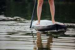 Clouse-op van een vrouwenbenen op paddleboard Royalty-vrije Stock Afbeeldingen
