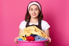 Clouse su di bella casalinga, lavorando circa la casa, tiene il bacino rosa enorme in pieno di tela sporca, sembrare sorpresa all fotografie stock
