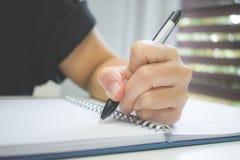 Clouse su Una penna della mano che scrive sul libro vicino alla finestra fotografie stock