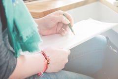 Clouse-up女性手写在笔记本的,轻定调子 免版税库存照片