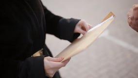 Clouse-up男性间谍寄发秘密文件到妇女,而不是接受与金钱的信封 行业 影视素材