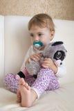 Clouse-up画象小孩子坐床在拥抱一只被充塞的玩具狐猴的屋子里 免版税库存照片
