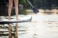 Clouse-up av en kvinna lägger benen på ryggen på paddleboard Fotografering för Bildbyråer