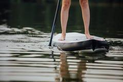 Clouse-up av en kvinna lägger benen på ryggen på paddleboard Royaltyfria Bilder