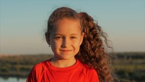 Portrait happy beautiful little girl smiling looking in the camera, on the sunset at outdoors. Stock footage. stock video footage