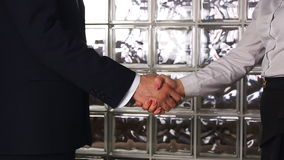 Clouse-up of businessman and  businesswoman shaking hands. In office stock video footage