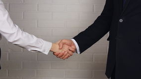 Clouse-up of businessman and  businesswoman shaking hands. In office stock footage