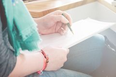 Clouse-up of female hands writing in notebook, light toning royalty free stock photos